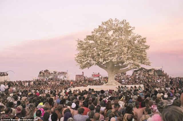 Thousands gather at near a constructed art installation replicated to look like a tree at this year's Burning Man festival