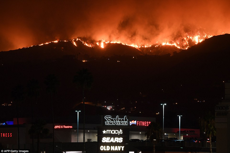 La Tuna Fire is seen raging behind the Burbank Town Center Mall early morning Saturday as fire and smoke burns the hills