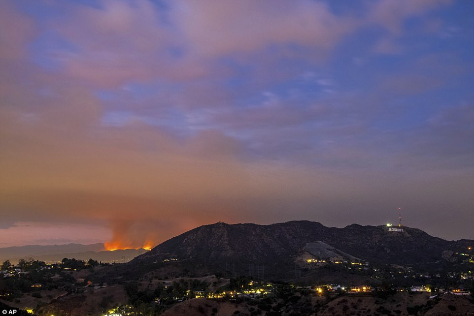 La Tuna Fire rages behind the Hollywood Hills on Friday, with the famed Hollywood sign in the front, right