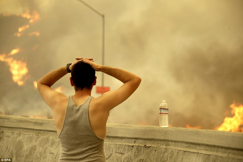 A resident stops along the 210 Freeway to check on his home and survey the fire and smoke engulfing areas of Sunland