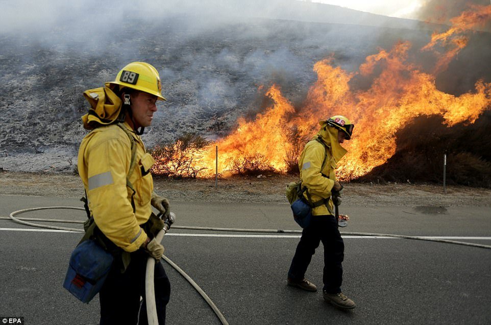 Firefighters monitor the LaTuna fire burning alongside the 210 freeway in Sunland where flames are shown licking the side of a hill