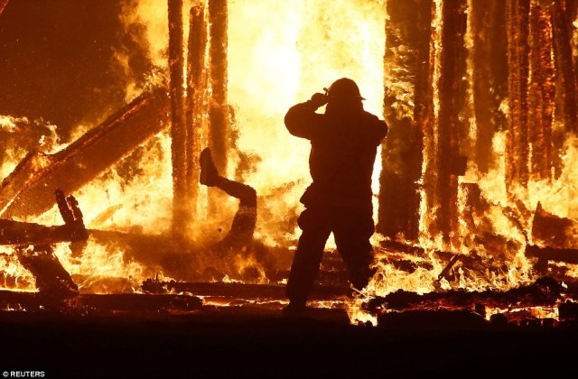 "A firefighter watches as a Burning Man participant (L) evades a chasing firefighter and falls into the flames of the ""Man Burn"""