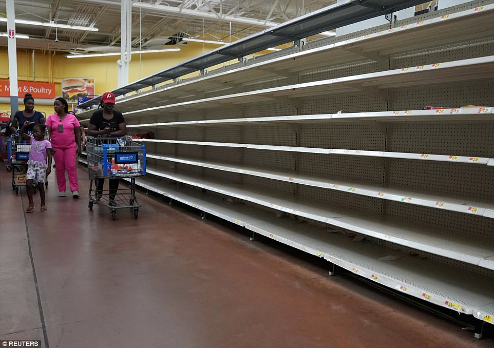 People walk past empty shelves where bread is normally sold in a Walmart store ahead of Hurricane Irma's expected arrival in North Miami Beach