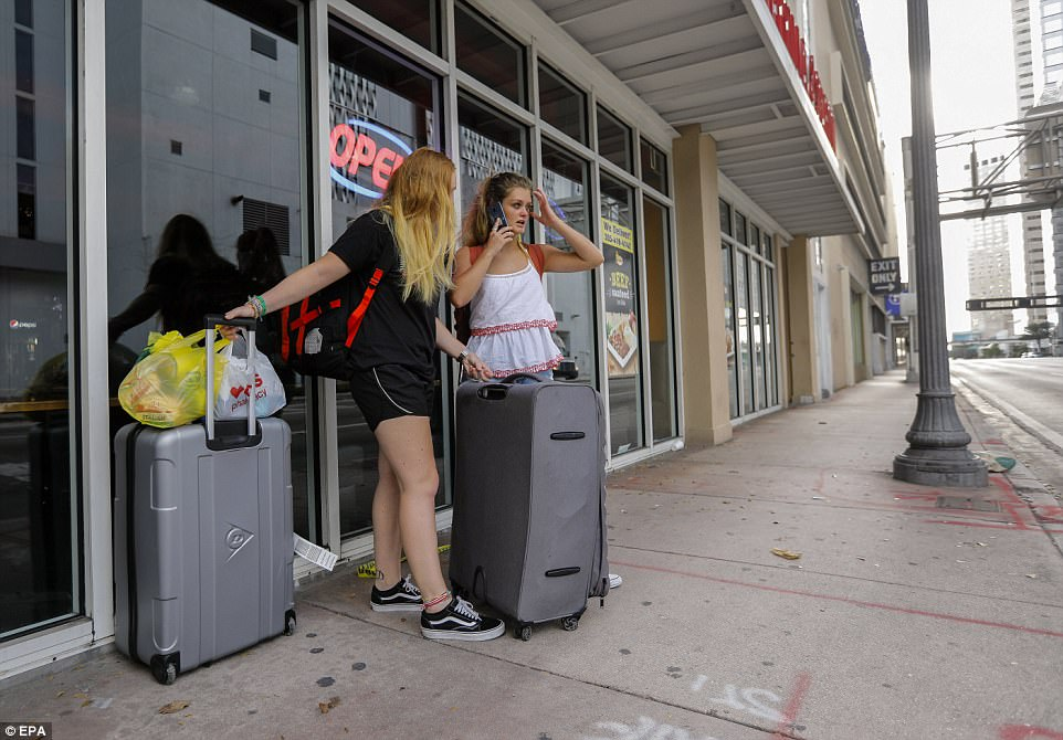 British tourists wait for a ride as they leave ahead of the expected arrival of Hurricane Irma in Miami, Florida on Friday
