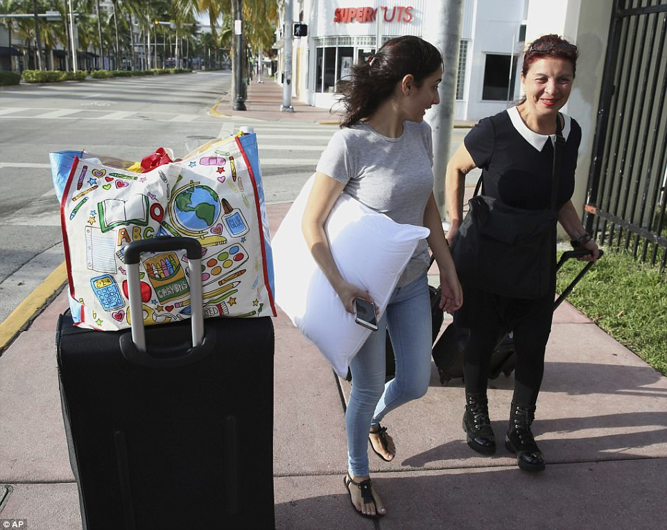 Amy Nacollari, left, greets her friend Mandy Varna at a bus stop in Miami Beach, Florida, Friday, September 8, 2017