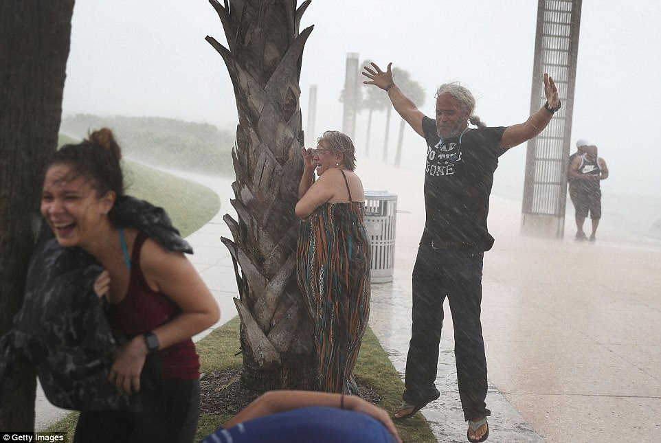 People in Miami Beach, Florida, ignore warnings to stay indoors on Saturday and brave the rain as Hurricane Irma approaches