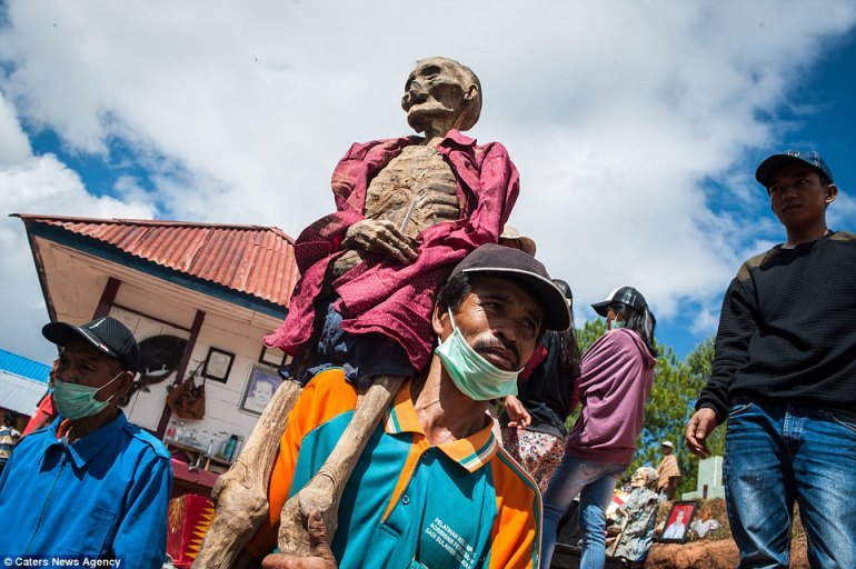 The body of a woman named Rapong, who died in 1990, is carried through the streets of Panggala Village. Torajan people do not view the deceased as dead until they are buried - which can take place weeks, months, or even years after they pass away, and instead keep the bodies at home and treat the person as if they were sick
