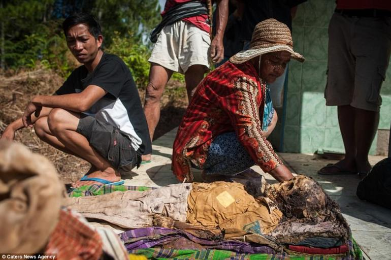 The body of a child is exhumed from a grave in South Sulawesi during the Manene ritual. The Torajan view death as another stage of life, and their relationships with the dead continue for years after they pass away