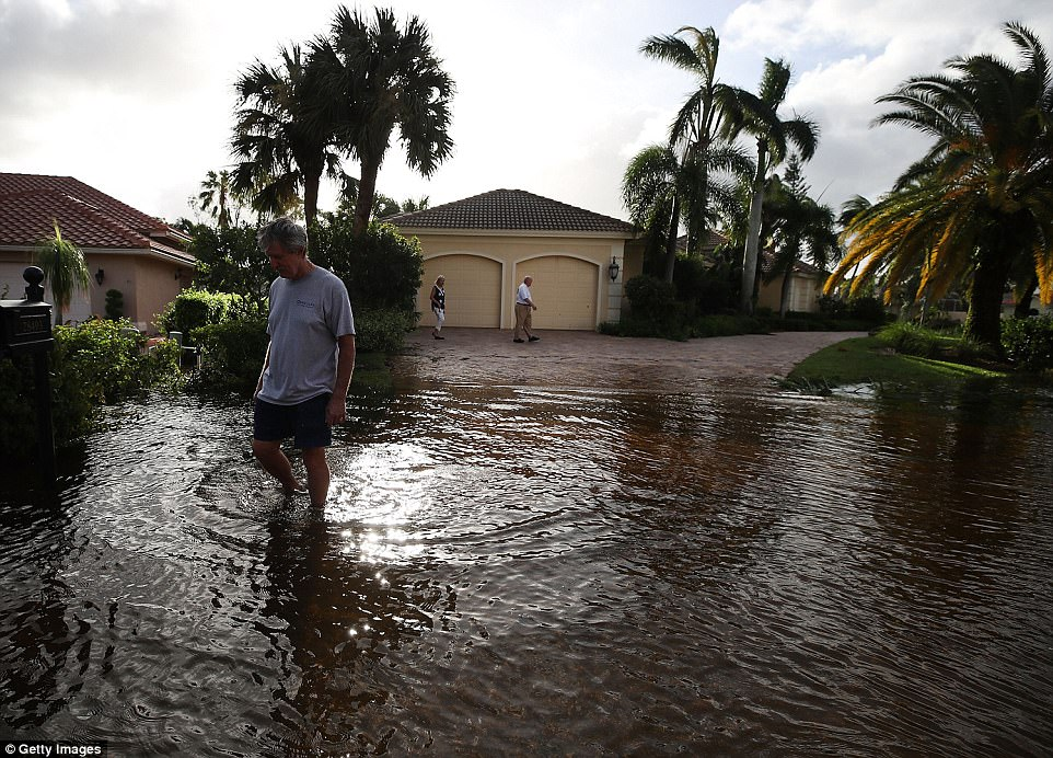 People inspect their neighborhood that was flooded by Hurricane Irma on September 11, 2017 in Bonita Springs, Florida