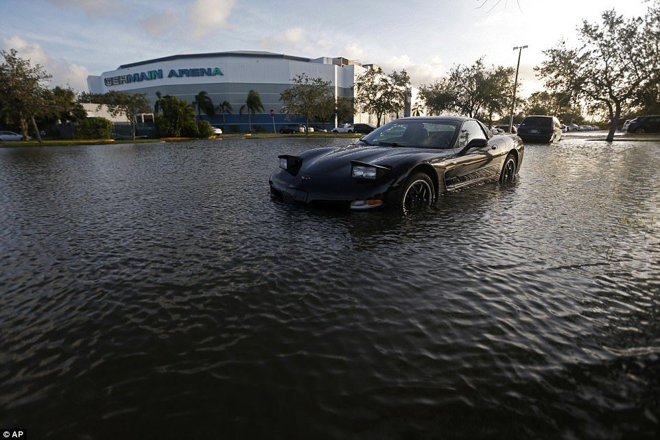 A car sits in a flooded parking lot outside the Germain Arena, which was used as an evacuation shelter for Hurricane Irma, which passed through yesterday, in Estero, Florida on Monday