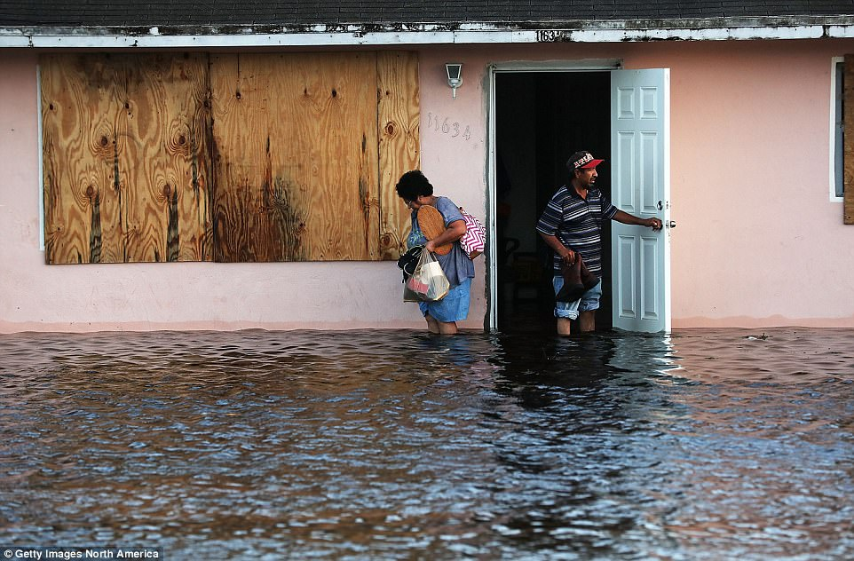 A couple leave their flooded home the morning after Hurricane Irma swept through the area on September 11, 2017 in Fort Myers, Florida