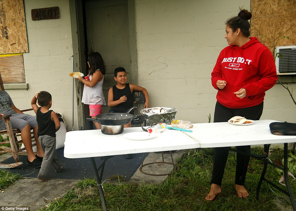 With power out to her entire neighborhood and the surrounding area Marissa Calderon uses a gas grill to make scrambled eggs, hotdogs and tortillas for her brother and young cousins, on September 11, 2017 in Bowling Green, Florida