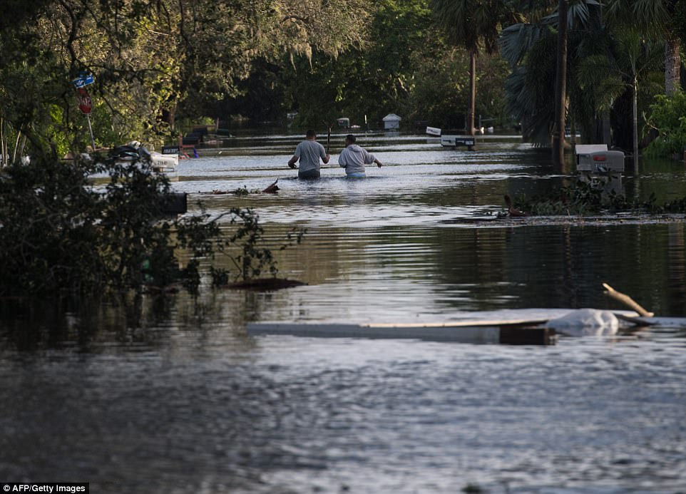People wade through a flooded neighborhood in Bonita Springs, Florida, northeast of Naples, on September 11, 2017, after Hurricane Irma hit Florida