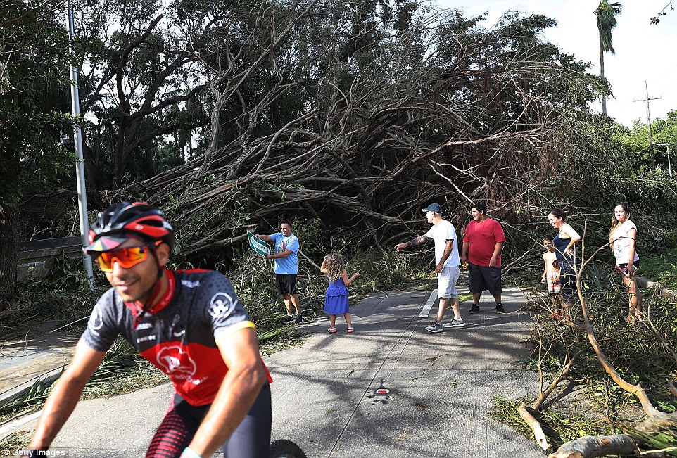 People move around branches and trees that were downed when hurricane Irma passed through the area on September 11, 2017 in Miami, Florida