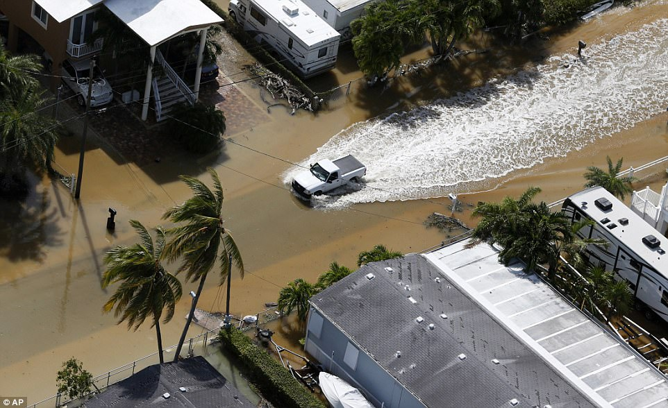 A pickup truck drives through a flooded area of Key Largo, Florida on Monday