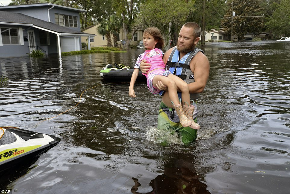 Tommy Nevitt carries Miranda Abbott, 6, through floodwater caused by Hurricane Irma on the west side of Jacksonville, Florida on Monday