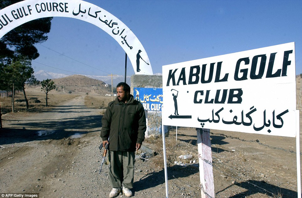 An armed Afghan security guard stands beside the entrance to the Kabul Golf Club