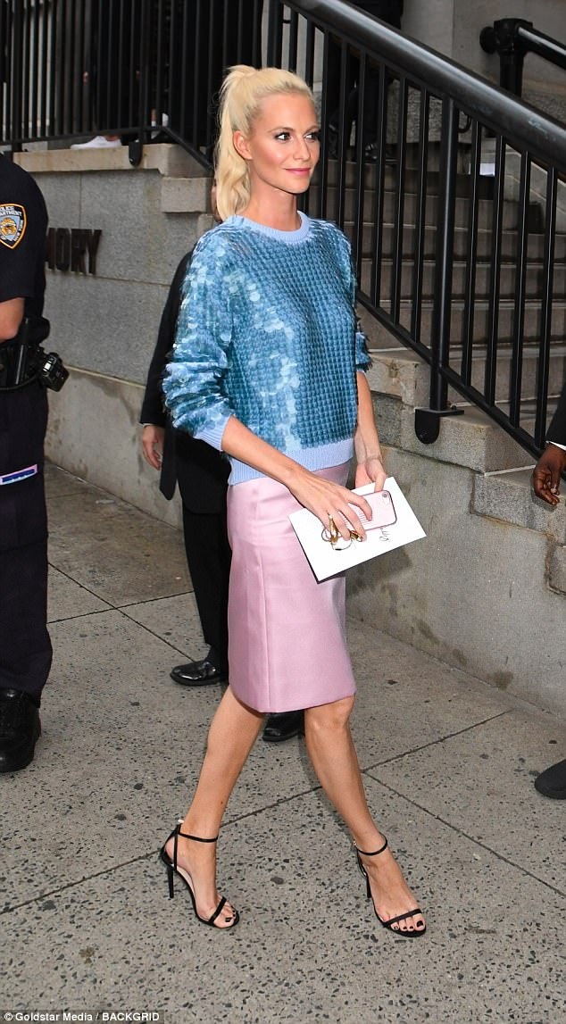 Saved: But the model kept her cool, looking stunning in a pretty pink pencil skirt and sequinned baby blue jumper. She gave a dazzling smile as she clutched her invite to the  show