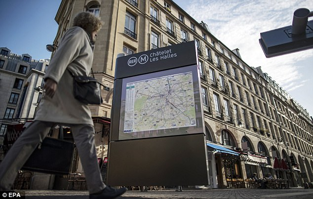 Pedestrians walk past the 'Chatelet Les Halles' metro station  where a soldier was attacked by a knife-wielding man in the early hours of the morning