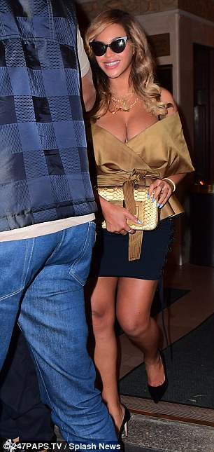 Gorgeous in gold: Beyoncé's daring low cut top ensured she won her own share of the plaudits as she made her way towards a waiting car