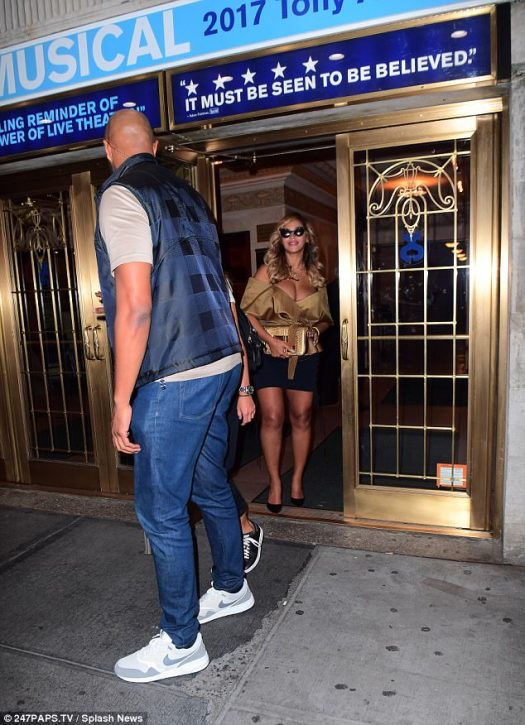 This way please: A minder walked ahead as the R&B superstar exited the Broadway theatre