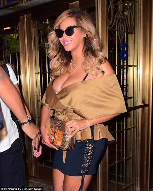 Striking:The R&B superstar looked stunning in a gold wrap-blouse that fully exposed her cleavage as she arrived at New York¿s Music Box theatre, where she took in a performance of Tony award winning musical Dear Evan Hansen