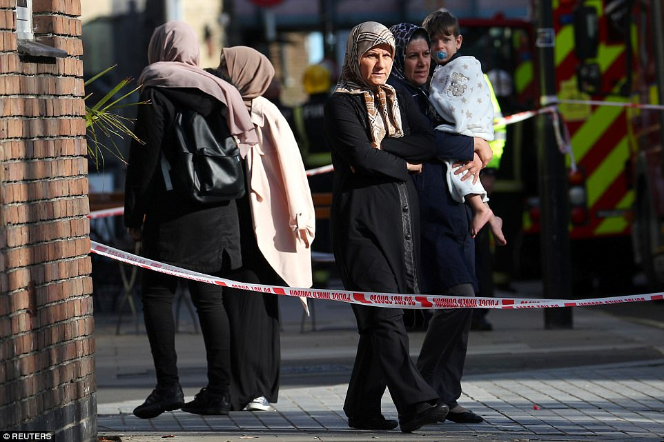 A family with young children look towards the station in the aftermath of the terror attack on London