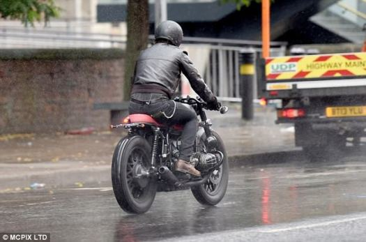 Off he goes:The former footballer looked every inch the biker pro in a leather jacket and helmet as he sped around the rainy city streets while filming an advert