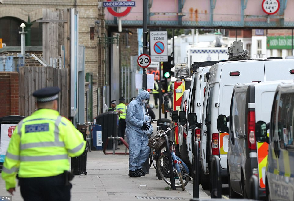 A forensic officer outside Parsons Green station in West London where there remains a heavy police presence as the manhunt for the suspected terrorist continues
