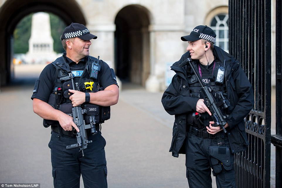 Armed police pictured on guard in Westminster after the UK's terror threat level was raised to severe - the highest level