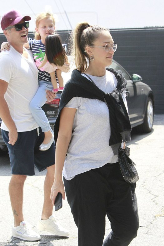 Bumping along: She dressed her baby bump in a grey t-shirt with a cardigan worn around her shoulders