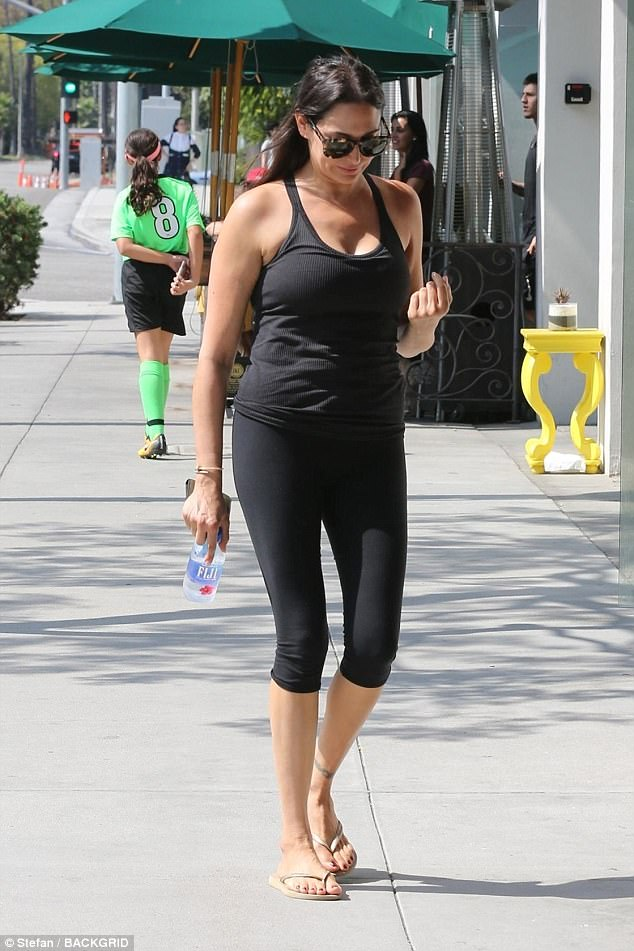 Monochrome maven:Lauren mirrored his casual vibe in a simple black vest and skintight leggings teamed with nude flip flops