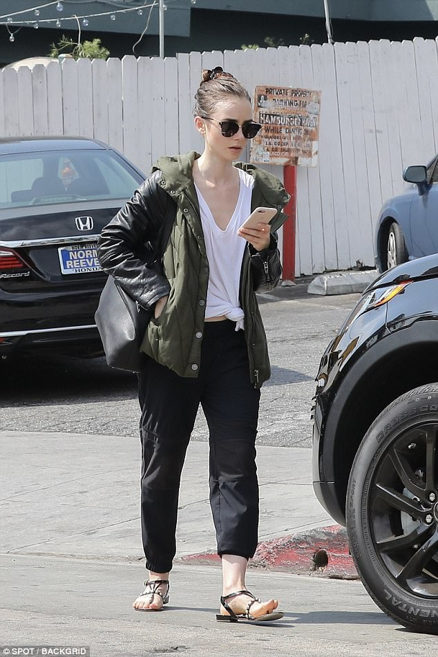 Low-key: Lily Collins, 28, sported a casual look - flashing the tiniest peek of her stomach in a knotted white top and baggy trousers, as she headed out in Beverly Hills on Saturday