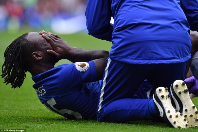 Victor Moses receives treatment for an injury picked up in a coming together with Arsenal striker Alexandre Lacazette