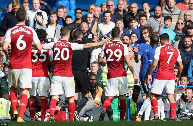 The Arsenal players surround referee Oliver as he shows Luiz a red card for the reckless challenge on Saed Kolasinac