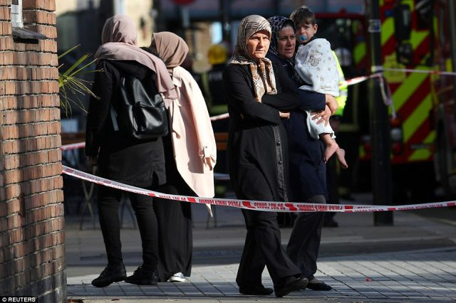 A family with young children look towards the station in the aftermath of the terror attack on London on Friday morning