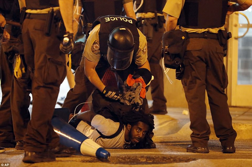 Police arrest a man in St Louis as demonstrators march in the city. In total 80 people were arrested on Sunday night - many of them for refusing to disperse at the orders of police