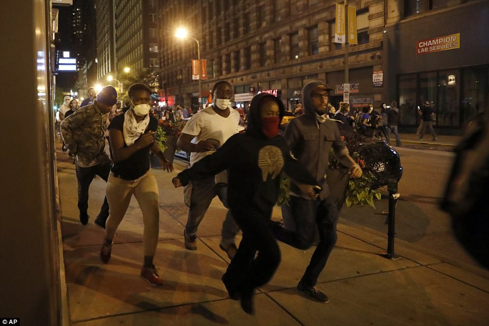 Chaos took over St Louis streets for the third night in a row on Sunday, as crowds continued to protests white ex-cop Jason Stockley's acquittal for the 2011 murder of Anthony Lamar Smith. Pictured: people running as demonstrators march