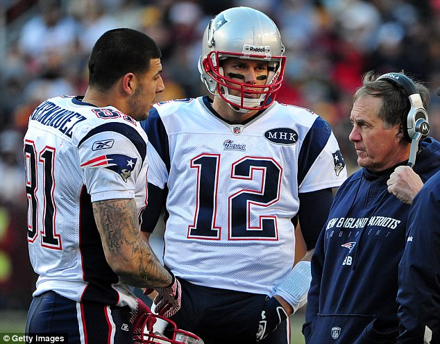 Hernandez (left) talks with Tom Brady (center) and Bill Belichick (right) during a game in 2011