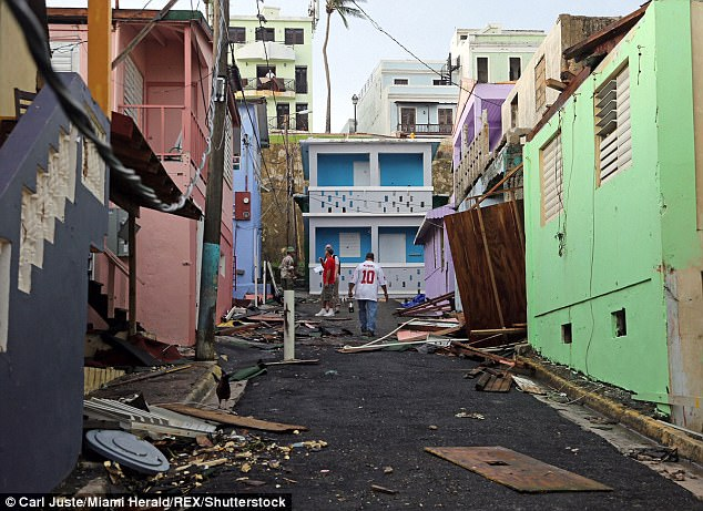 The storm has so far claimed the lives of seven in Puerto Rico (Pictured, men walk up near colorful damaged buildings in San Juan's 'La Perla' neighborhood on Friday)