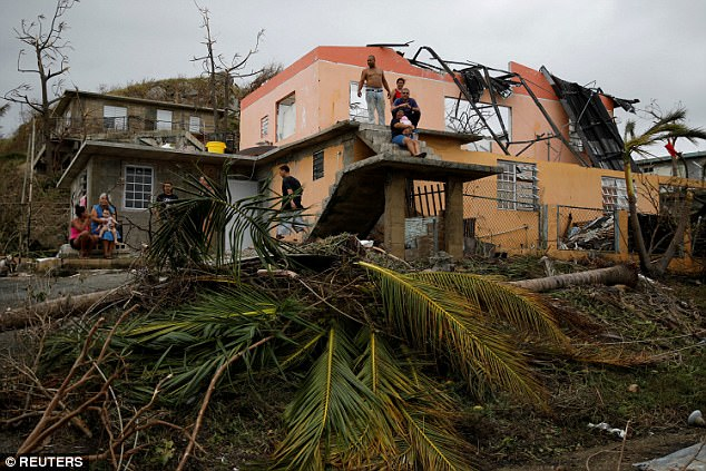 The hurricane was expected to tally $30billion in damage and lost economic activity in Puerto Rico (Pictured, people rest outside a damaged house in Yabucoa, Puerto Rico, on Friday)