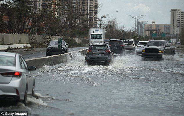 Vehicles drive along a flooded road in San Juan after Hurricane Maria passed through the area on Saturday