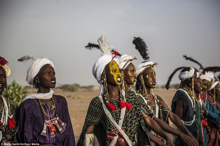 Women wearing brightly-coloured face paint chant and pull faces as they take part in the traditional courtship ritual in Niger