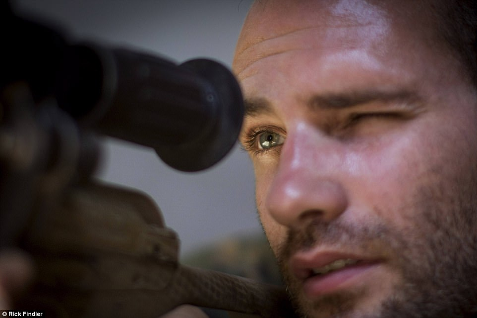 Macer looks through his sniper rifle's scope in Raqqa, Syria.Macer, who went to Kimbolton School in Huntingdon,  said his mere presence serves as a morale booster because it shows a British man cares about the people of Syria