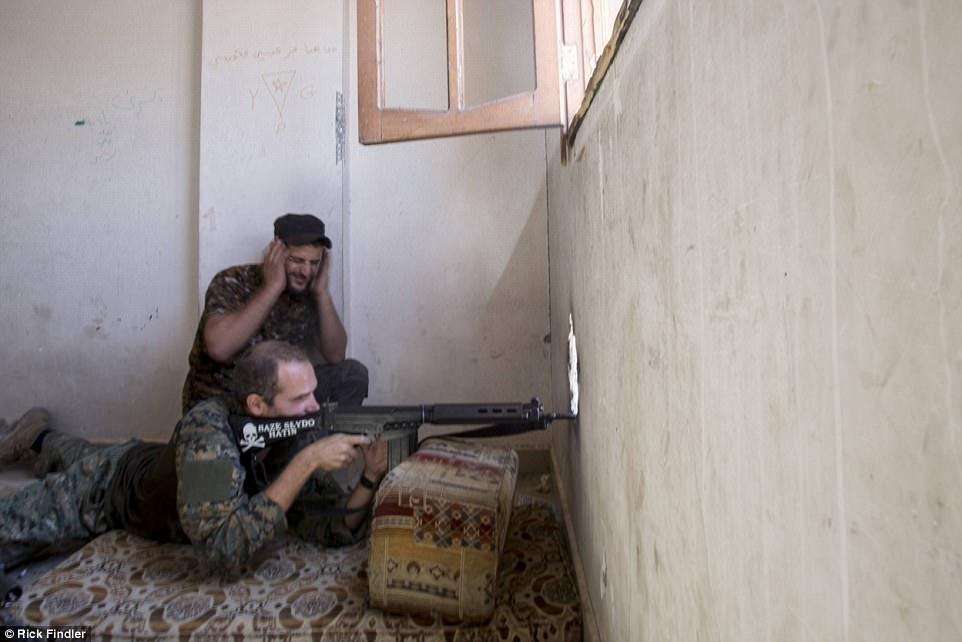 Macer fires his sniper rifle toward ISIS militants from a tower block on the outskirts of Syria