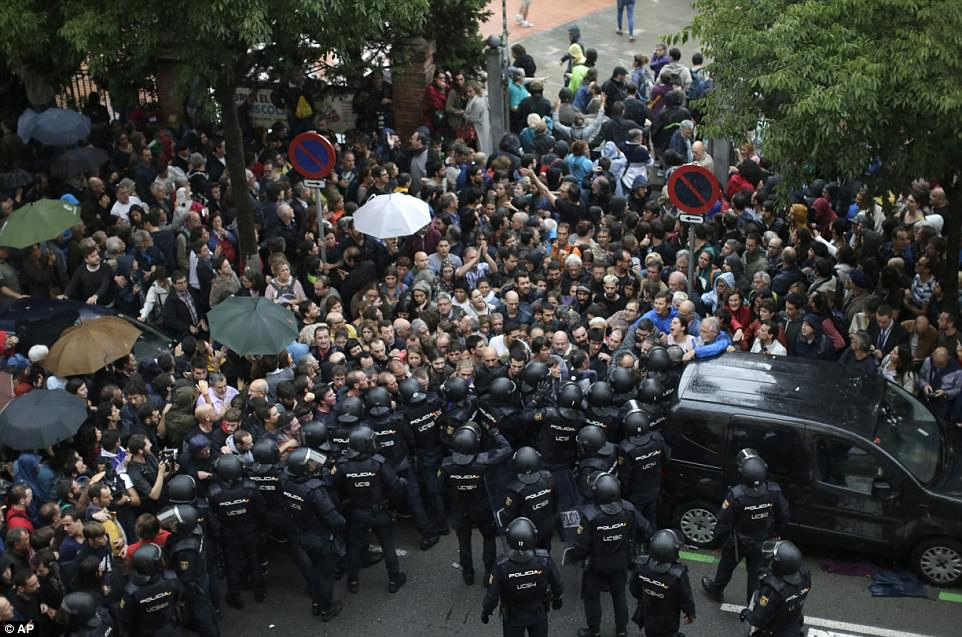Spanish National Police prevents people from entering a voting site for the controversial referendum in Barcelona