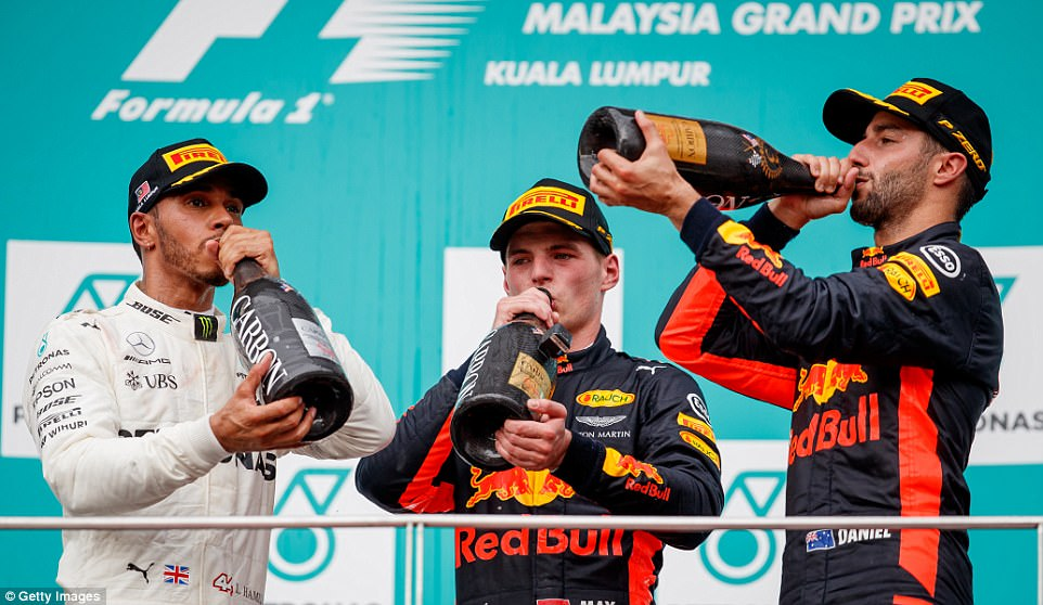 Hamilton, who came second on Sunday, celebrates on the Malaysian Grand Prix podium alongside the Red Bull pair