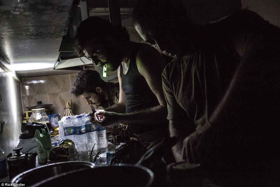 MFS soldiers cook a late dinner in the kitchen of an abandoned house on the front lines of Raqqa. They are using the house as their Nocter (a base which is being used to hold the line of their forces against ISIS)