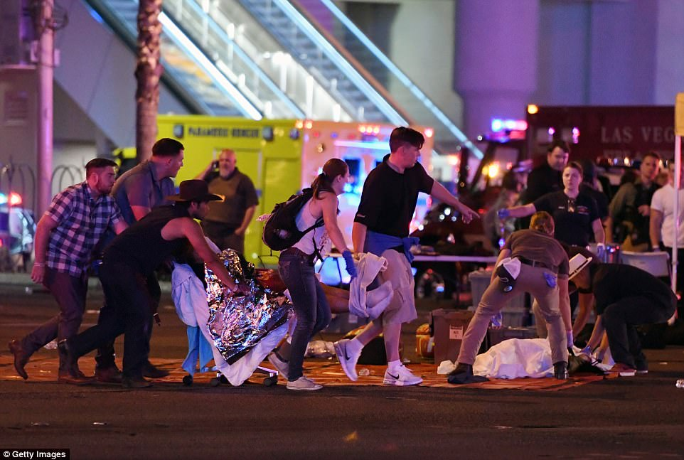 First responders and bystanders carry an injured person to an emergency station located at the intersection of Las Vegas Boulevard and Tropicana Ave - one block north of the shooting