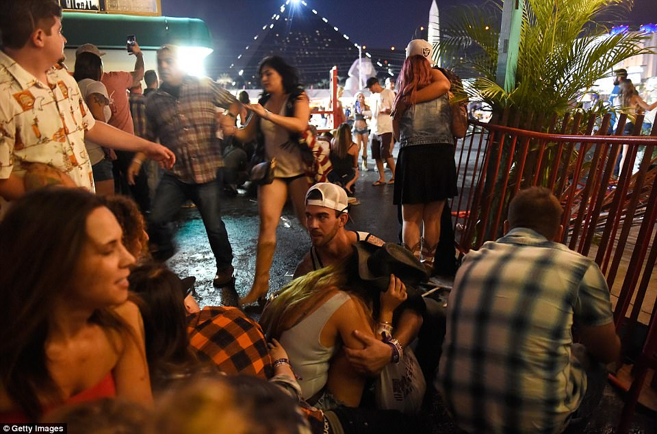Festival-goers, crouch in cover at the Route 91 Harvest country music festival after gunfire rained down on crowds